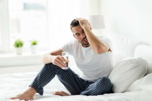 young adult man waking up hangover headache